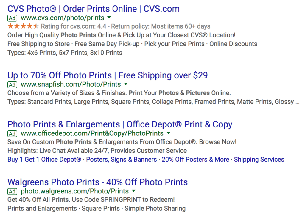 Google search ad copy about photo prints with the percentage off in their headlines.